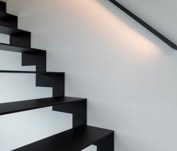 Escalier avec éclairage LED sous la rampe dans une maison contemporaine