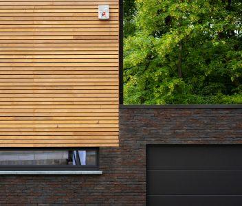 Parement en bois sur la façade avant d'une maison contemporaine à Beaufays